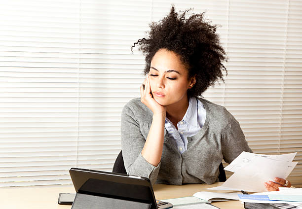 curly-haired woman doing paperwork stock photo