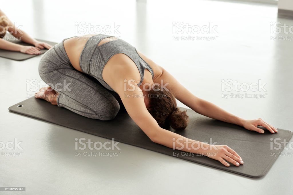 Curlyhaired Woman In Sports Bra Lying On Yoga Mat While Resting In Childs Pose Stock Photo Download Image Now Istock
