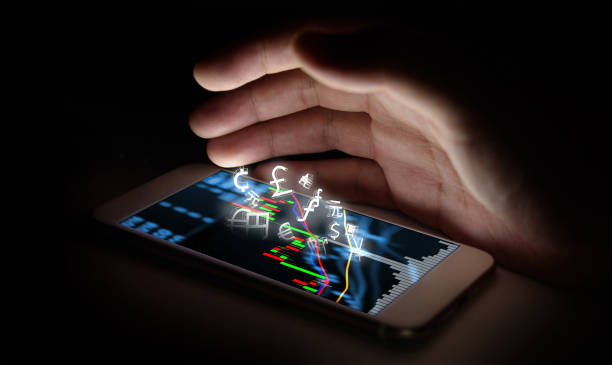 Currencies sign icon and smartphone with stock market graph screen and finger with black background. Blockchain , Fintech Investment Financial Internet Technology Concept. stock photo