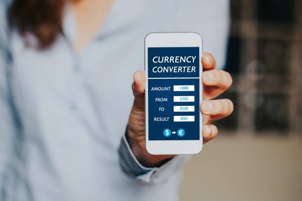 währung-konverter mobile app in ein handy-displays. frau zur kamera zeigt. - adapter stock-fotos und bilder