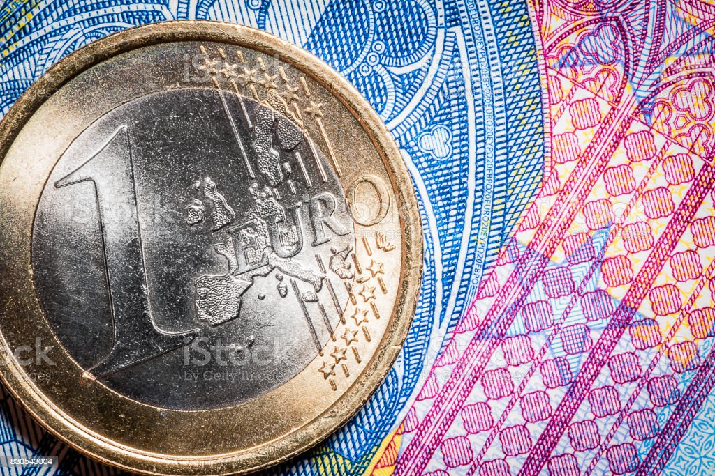 Currency money macro: 1 Euro coin on 20 Euro banknote stock photo