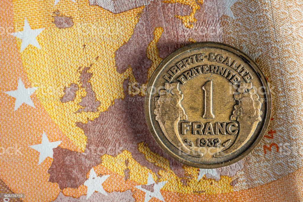 Currency money macro: 1 French franc coin on 50 Euro banknote stock photo