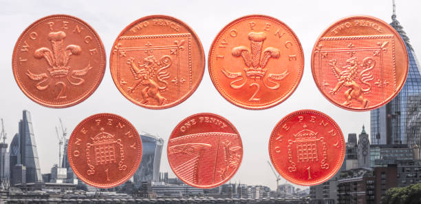 uk currency one and two pence coins london skyline - whiteway money stock photos and pictures