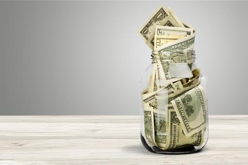 Glass jar for money on background