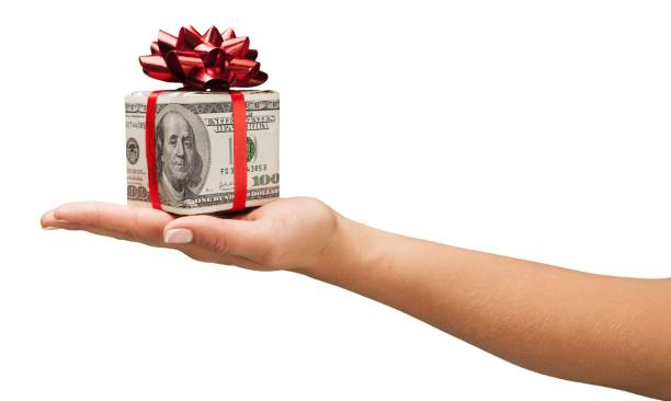 Currency. Human hand holding christmas present wrapped in dollar banknotes isolated on white expense stock pictures, royalty-free photos & images