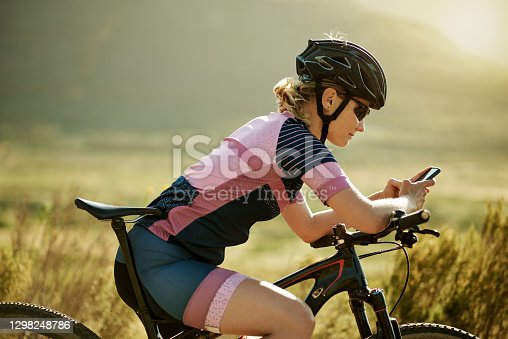 Shot of a sporty woman using her cellphone while out cycling on a country road