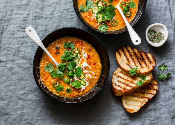 curried red lentil tomato and coconut soup - delicious vegetarian food on grey background, top view. flat lay served healthy lunch - sopa imagens e fotografias de stock