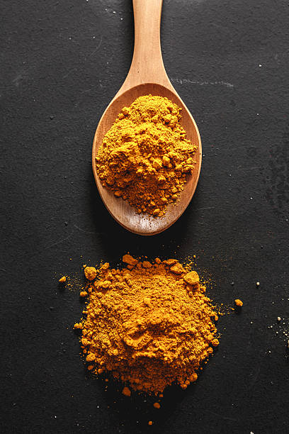 Curry in wooden spoon Curry in wooden spoon with black background. curry powder stock pictures, royalty-free photos & images