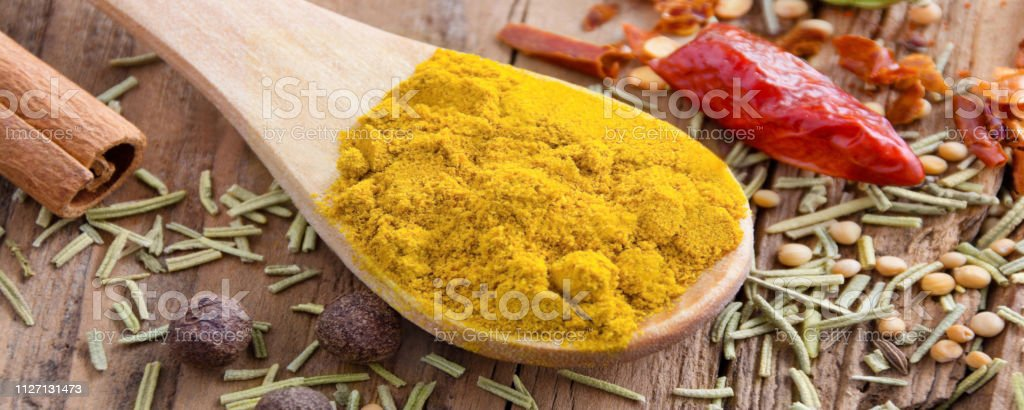 Curry powder and spoon against a wooden a background
