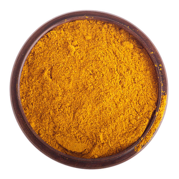 Curry powder in brown bowl isolated on white background stock photo