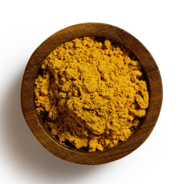 curry pulver i mörkt trä skål isolerade på vitt från ovan. - saffron on white bildbanksfoton och bilder