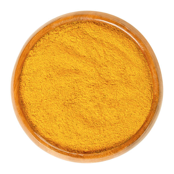 Curry powder in wooden bowl over white stock photo