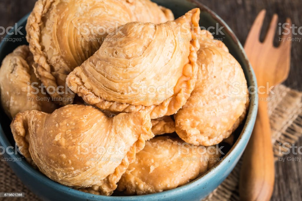 Curry puff in blue bowl on old wooden table stock photo