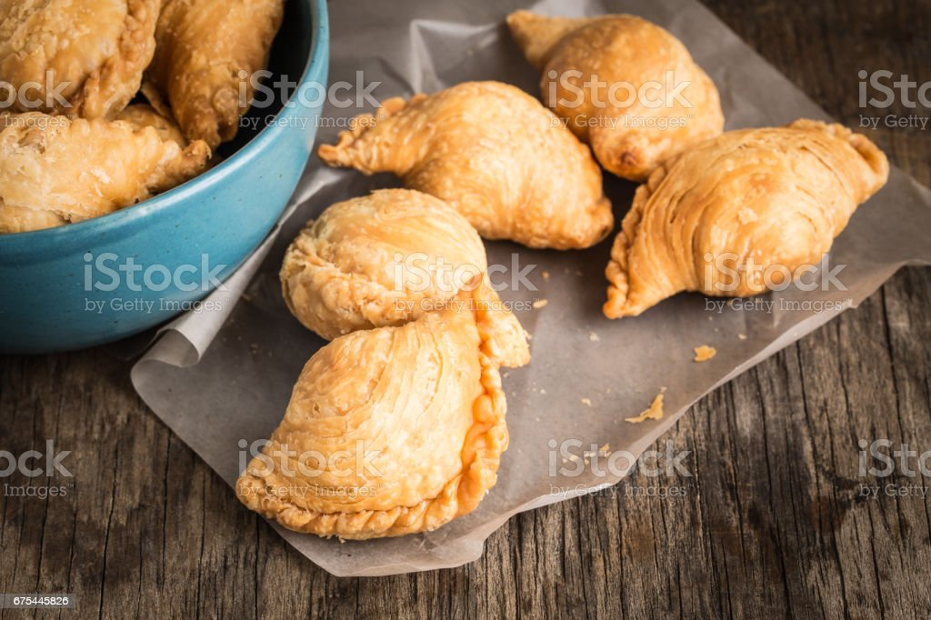 Curry puff on paper on old wooden table stock photo