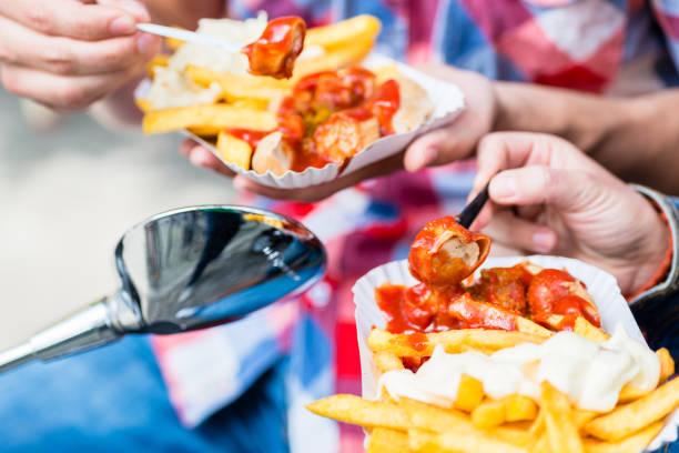 currywurst mit pommes frites auf roller - currywurst stock-fotos und bilder