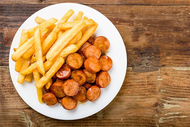currywurst with fries on a wooden background - currywurst stock-fotos und bilder