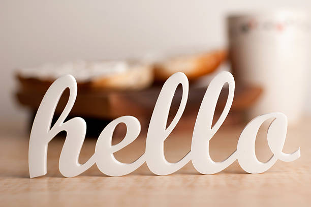 cursive hello sign with blurred breakfast in background - welcome stock photos and pictures