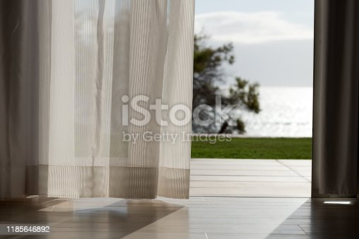 curtain in wind with view to palms and beach