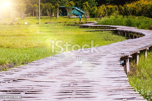 istock Curve Bamboo Bridge. Curved wooden bridge at park in paddy field 1323073130