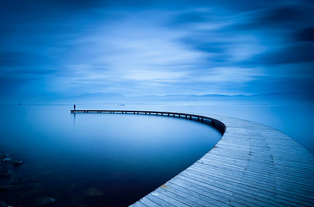 curve of the jetty and man - nature foggy calm bildbanksfoton och bilder