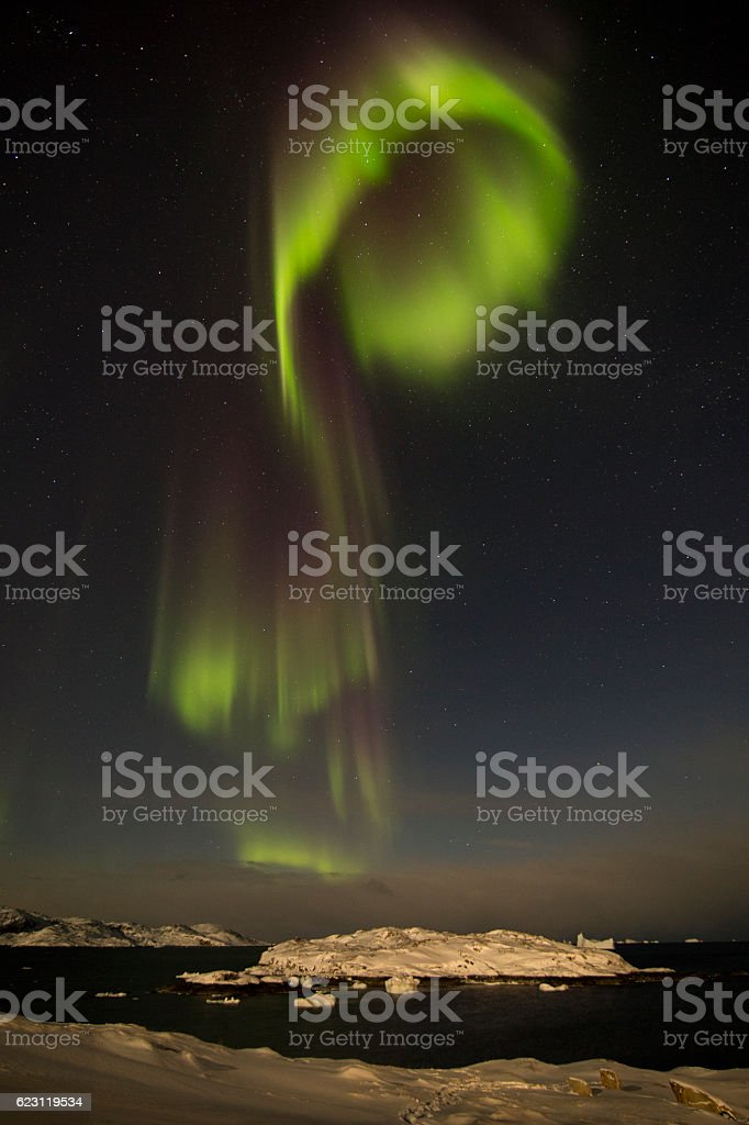 curved Aurora Borealis over snow covered island stock photo