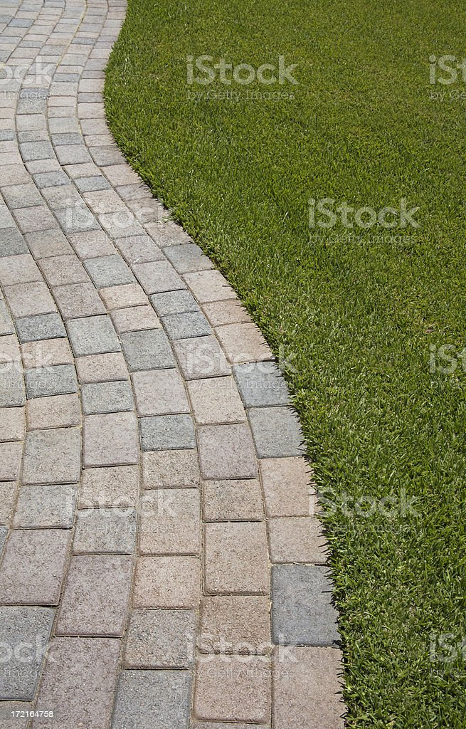 A curved brick pathway along some grass stock photo
