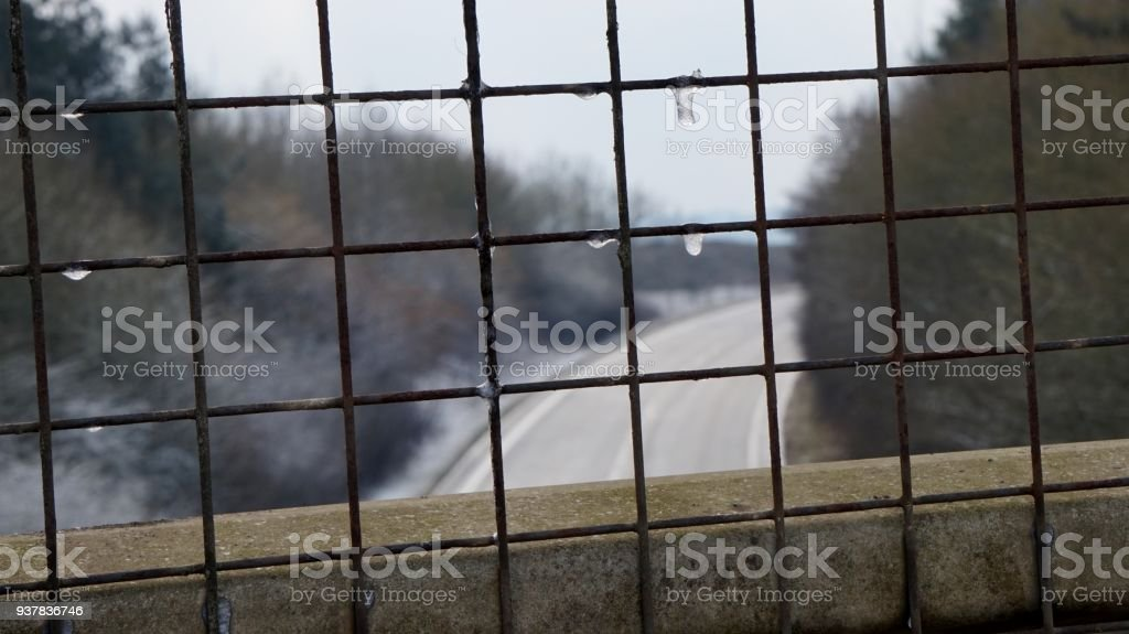 Curved country road from above viewed through wired mesh in winter. stock photo