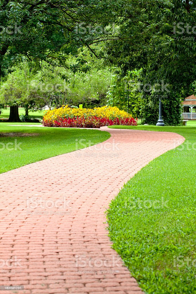 Curved Garden Path of Bricks with flowers and trees stock photo