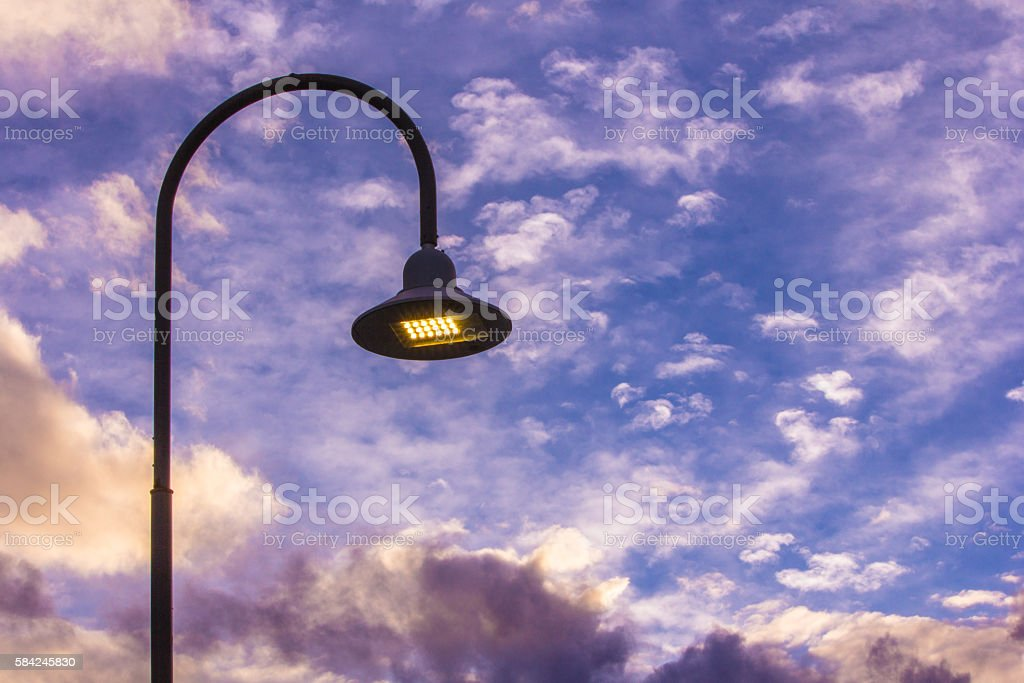 Curved lamppost in clouds stock photo