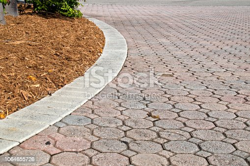 Child's eye view of octagon and square shaped brick pavers with curved section of driveway with rectangle bricks along edge showing plant and mulch pile. Curves to left.