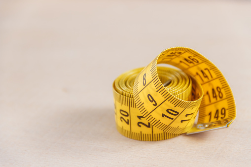 istock Curved measuring tape. Closeup view of yellow measuring tape. 658002842