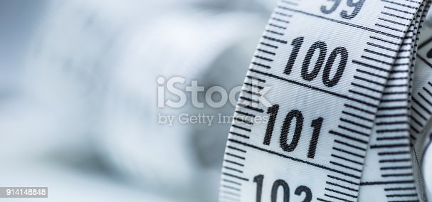 istock Curved measuring tape. Measuring tape of the tailor. Closeup view of white measuring tape 914148848
