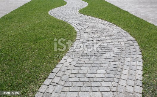 Curved path in the shape of a wave on the grass in the Park. Paved with tiles of different shapes.