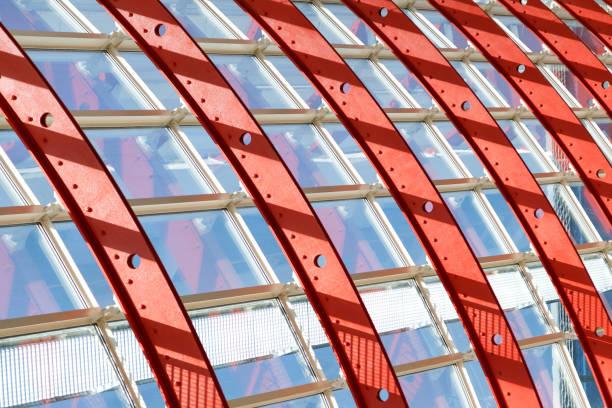 Gekrümmte rote und weiße Metallstrukturen halten die Fenstersysteme. Durch das Glas geht helles Sonnenlicht. Abbildung der Festigkeit und Luftigkeit der Eisenstruktur. – Foto