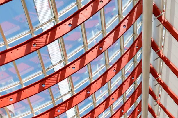 Gekrümmte rote Metallbalken mit Perforation halten die Fenstersysteme. Durch das Glas geht helles Sonnenlicht. Architektonische Rhythmus-Illustration. – Foto