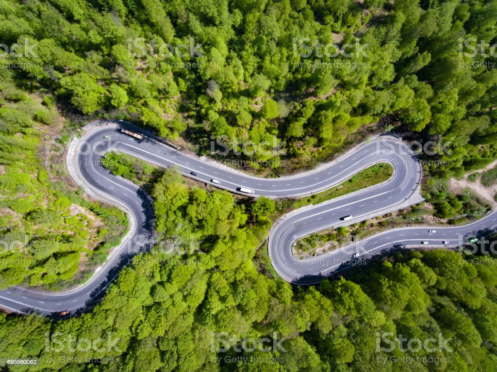 Curved road in the forest. Transylvania, Romania, Europe. Cars passing on road. stock photo