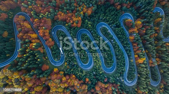 Curved road trough the forest. Pass in Transylvania, Romania. Aerial view from a drone.