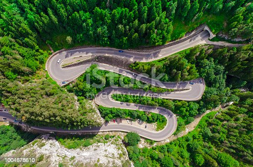 istock curved road with cars and beautiful forest landscape. 1004678610