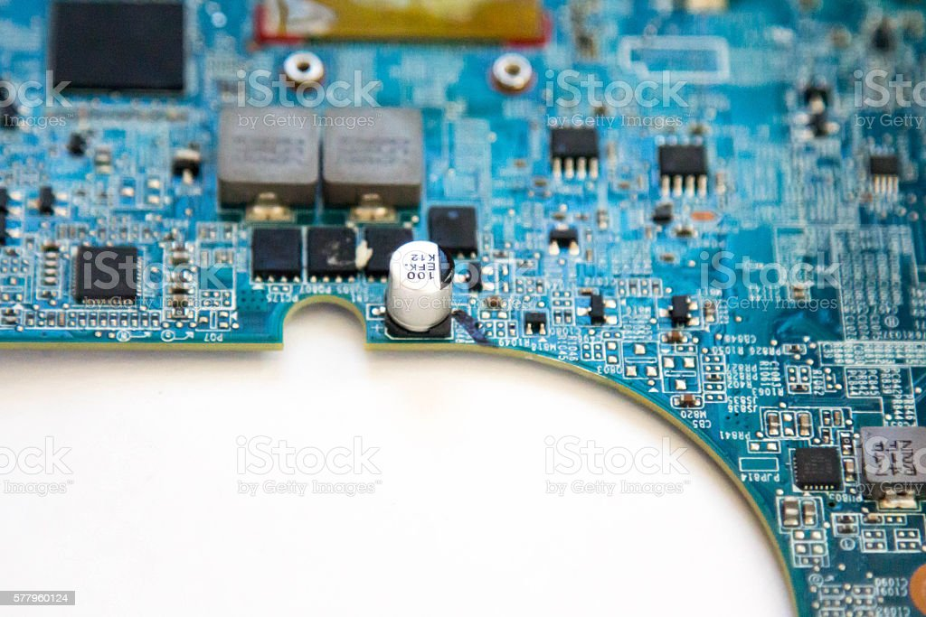 Curving edge of a circuit board covered in electrical components stock photo