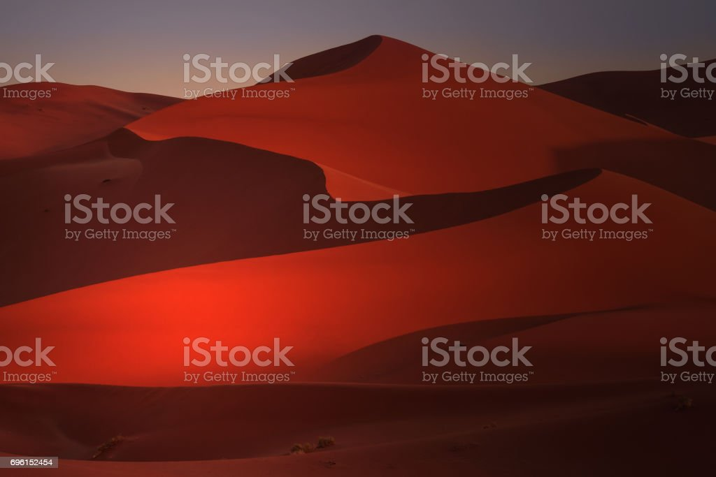 Curving lines and shadows of red sand dunes in Namibia at sunrise. stock photo