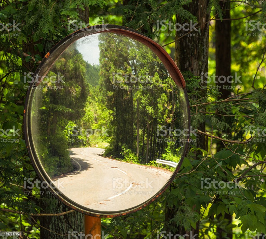Curving road reflected in safety mirror stock photo