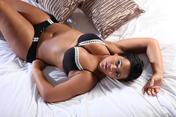 Curvy african american woman in bed lingerie stock photo