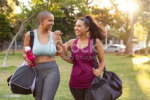Cheerful smiling friends in sportswear holding gym bag and bottle in park. Multiethnic women going to park for fitness workout. Two curvy girls walking after exercise session outdoor at sunset.