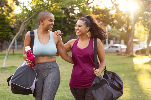 curvy friends walking home after fitness exercise - beautiful curvy girls stock photos and pictures