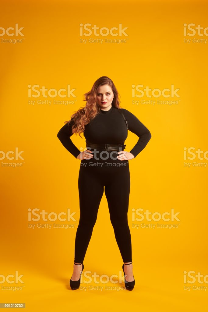 3eaff6e65db Curvy girl in tight-fitting clothes posing with her hands on hip - Stock  image .