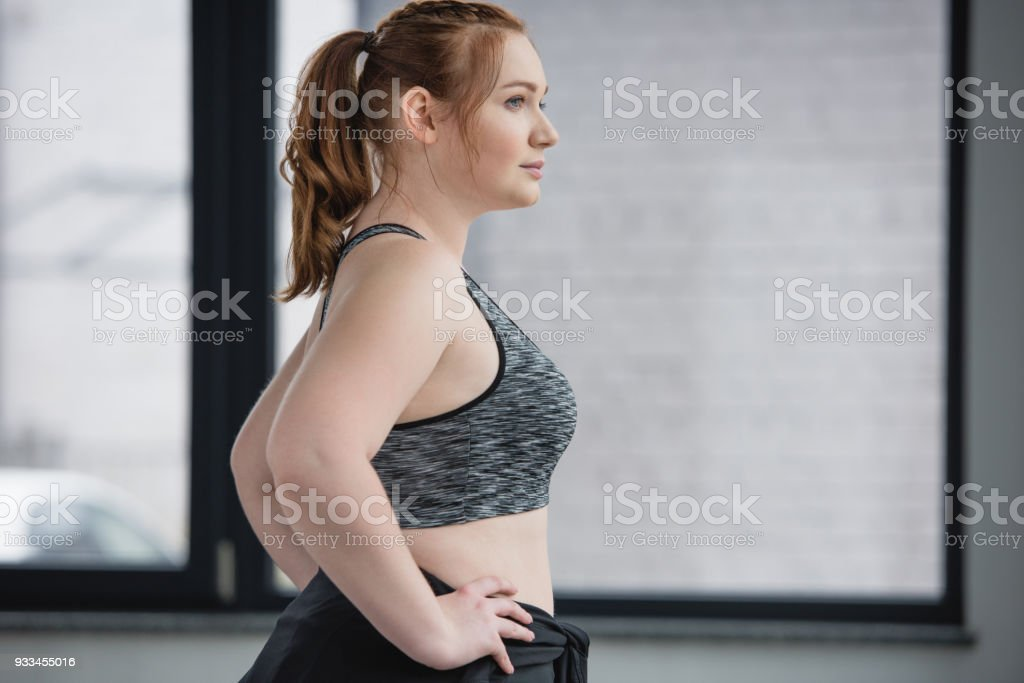Curvy girl wearing sports top in sports center