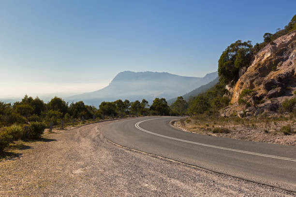 Curvy Olivers road at the curve with misty view of southern side of Mt Roland in background in Tasmania, Australia stock photo