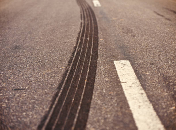 A curvy tyre marks on a street unique stock photo A black large vehicles tyre track on a street isolated unique stock photo tire track stock pictures, royalty-free photos & images