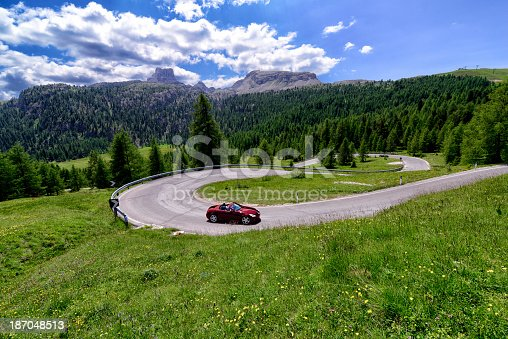 A sport car turning on a sharp S-bend on a rural mountain road.