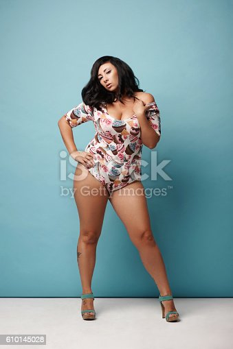498310066istockphoto curvy woman with raven hair in trendy combidress posing against 610145028